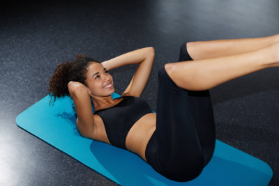 side view of smiling young woman working out at fitness center doing crunch abdominal sit-ups